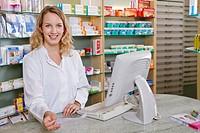 Germany, Brandenburg, Pharmacist holding prescription, smiling, portrait