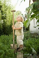 Germany, Bavaria, Boy holding shovel in garden