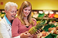 Germany, Cologne, Women with pineapple in supermarket