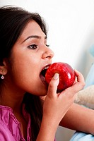 Close up a young woman eating apple
