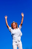 Carefree woman enjoying life against blue sky