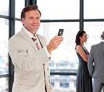 Portrait of a cheerful businessman on phone with his team