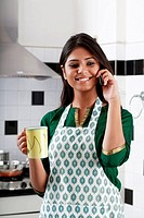 Woman holding a coffee cup and speaking on mobile phone