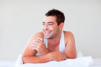 Man having a cup of coffee in bed