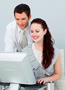 Businessman helping a businesswoman with a computer