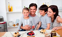Young family eating fruits and pancakes for breakfast