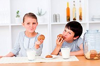 Siblings eating cookies and drinking milk