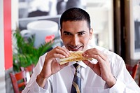 A young businessman having sandwich