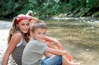 Children sitting by river in summer