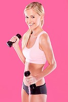 beautiful blonde fitness model on pink background