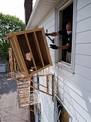 A man throws a wooden drawers out of a foreclosed house in Woonsocket, Rhode Island, United States