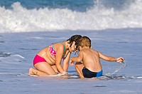 Blond child and girl at seaside, Crete, Greece