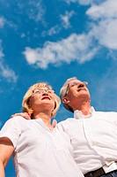 Glückliches älteres Paar blickt in den blauen Himmel