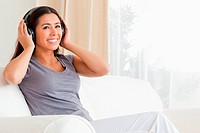 woman sitting on sofa with earphones looking up