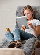 Beautiful girl relaxing at home, surfing the internet and looking at the screen of a touchpad