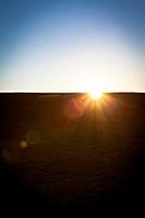 Sun behind a hill