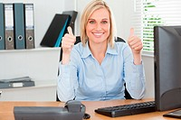 Young woman sitting behind desk with thumbs up