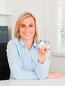 Gorgeous blonde businesswoman showing miniature house looking in