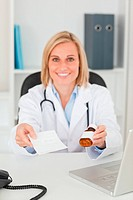 Smiling blonde doctor holding prescription and medicine looks in