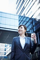 A business woman with a coffee cup between office buildings looking around