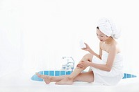 A woman with bath towel around her body and over head sitting at edge of bath tub putting lotion on her leg