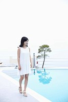 A woman in white dress next to a pool walking