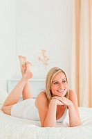 Portrait of a smiling woman posing on her bed