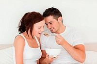 Man feeding cereal to his wife