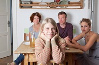 Girl in kitchen, sister and parents behind, Portrait,smiling