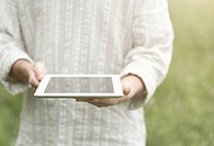 Man holding a digital tablet in a meadow