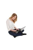 junge blonde frau sitzt mit notebook auf dem schoß