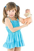 little girl depositing change in her piggy bank