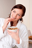 Happy woman in bathrobe holding cereals for breakfast