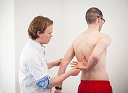 Sports medicine. Sports physician manipulating an athlete´s arm during a fitness assessment.