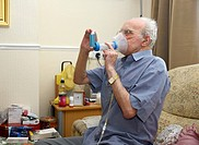 Bronchodilator inhaler with a spacer device is used at home by an elderly male patient with chronic obstructive pulmonary disease COPD. The inhaler pr...
