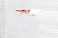 Brunette businesswoman peeking out of a window
