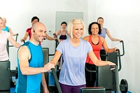 Fitness instructor leading gym people exercise