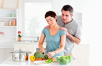 Man massaging his wife while she is cutting vegetables