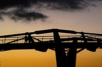 Silhouette of the Millenium Bridge and two pedestrians seen against a Winter sunset in London, England