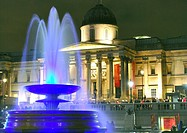 Fountain in Trafalgar Square, London, England, lit up colourfully at night, with the National Gallery illuminated in the background