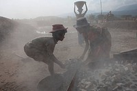 Stone workers throwing stones to the stone crusher machine in Bholaganj During monsoon season boulders, rocks, stones and pebbles wash up from India i...