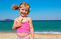 little girl with starfish posing on beach