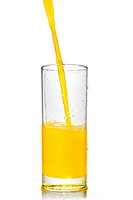 orange juice poring into glass isolated on white