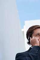 Businessman using cell phone outdoors, cropped