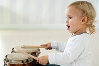 Baby boy playing drums, side view