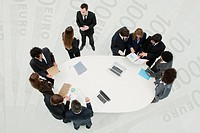 Business associates in meeting, standing on superimposed image of one_hundred Euro banknotes