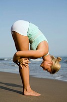 Young adult woman practicing yoga on the beach