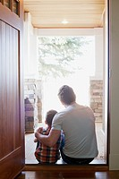 Father and son sitting in doorway