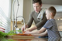 Dad and young son washing carrots in kitchen
