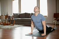 Man doing yoga poses at home